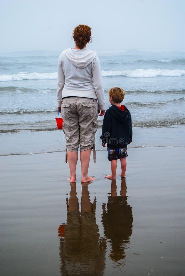 母亲和幼儿观看的波浪 免版税库存图片