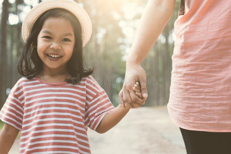 母亲和微笑着握手的逗人喜爱的儿童女孩 库存照片
