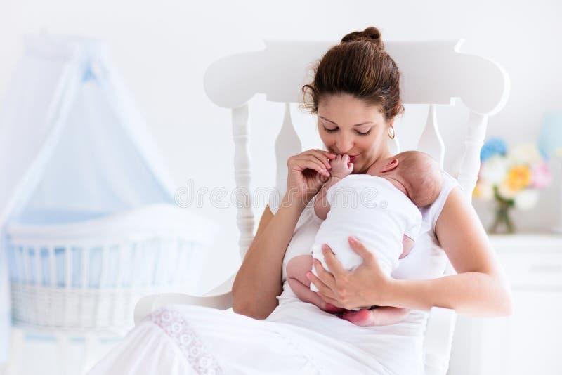 年轻母亲和新出生的婴孩在白色卧室 库存图片