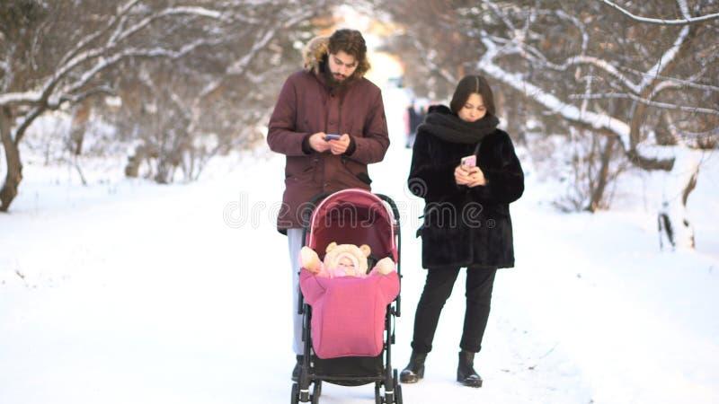 母亲和父亲使上瘾对忽略婴孩的手机婴儿推车的和,当走时在冬天公园 繁忙的父母 免版税库存图片