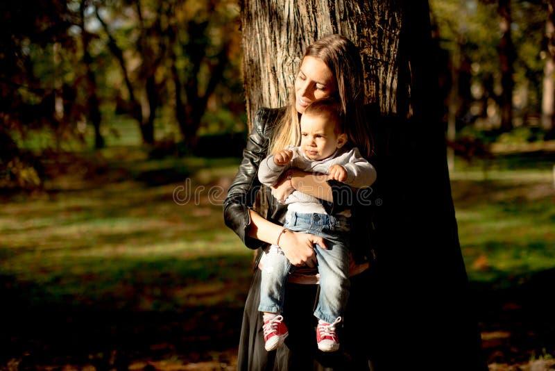 母亲和男婴在秋天公园 免版税库存照片