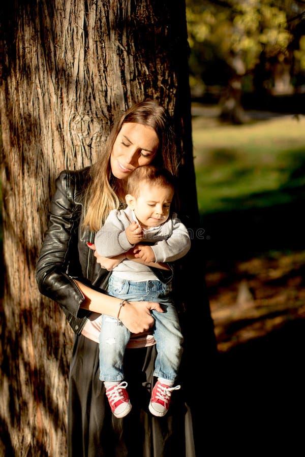 母亲和男婴在秋天公园 免版税图库摄影