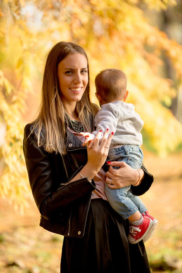 母亲和男婴在秋天公园 库存照片