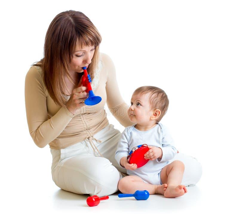 母亲和获得的男婴与音乐玩具的乐趣 免版税库存图片