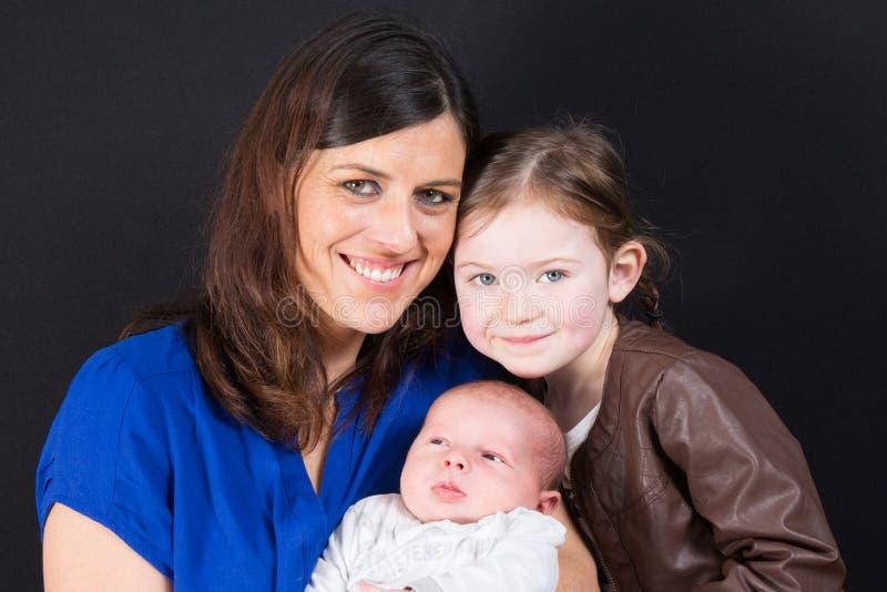 母亲和逗人喜爱的大姐女儿有新的新出生的小儿子的 免版税库存照片