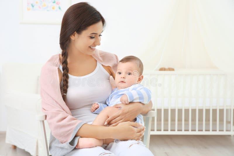 母亲和逗人喜爱的婴孩坐椅子在沐浴以后 图库摄影