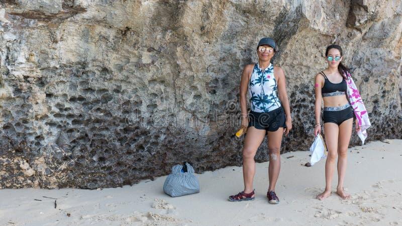 母亲和青少年的女儿身分在岩石墙壁前面 库存图片