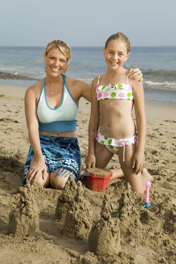 母亲和年轻女儿大厦沙子城堡在海滩 免版税图库摄影