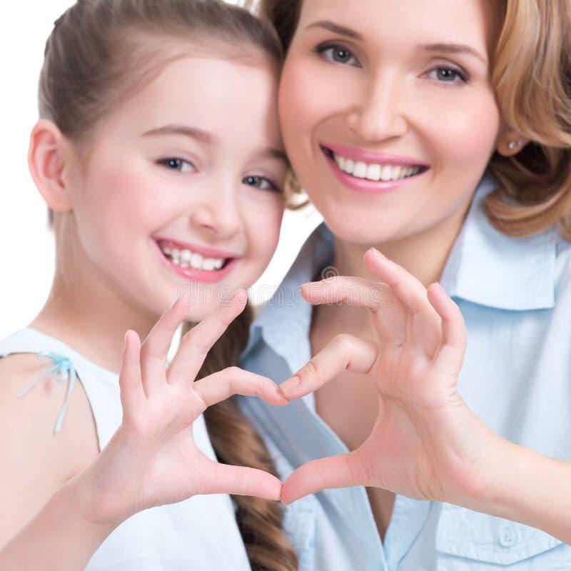 母亲和年轻女儿有心脏的塑造标志 免版税库存照片