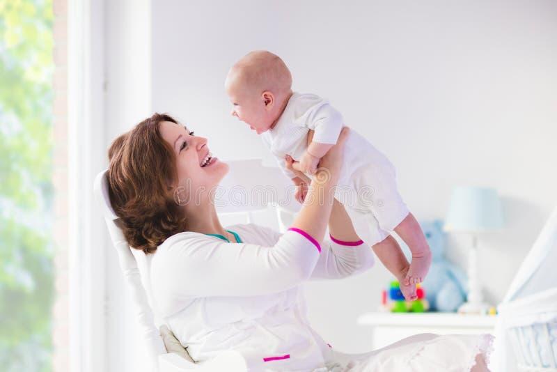 母亲和婴孩在白色卧室 免版税库存照片