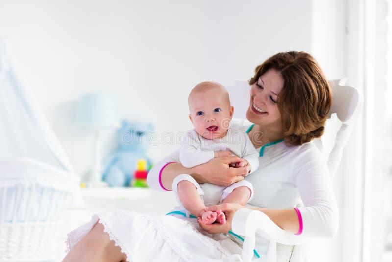 母亲和婴孩在白色卧室 免版税图库摄影