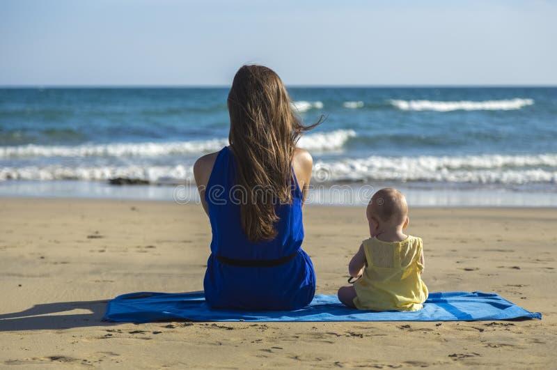 母亲和婴孩坐海滩 免版税库存照片