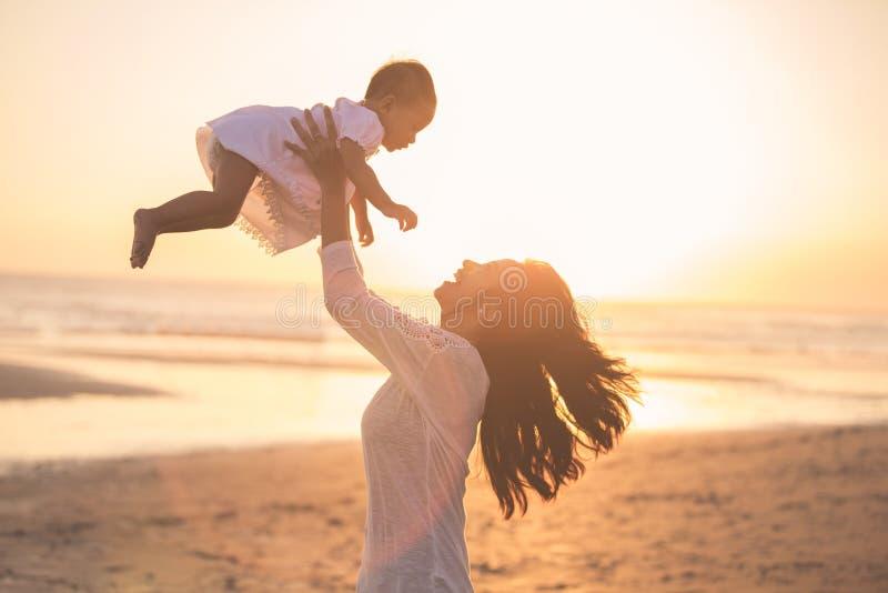 母亲和婴孩画象海滩的在日落 免版税库存照片