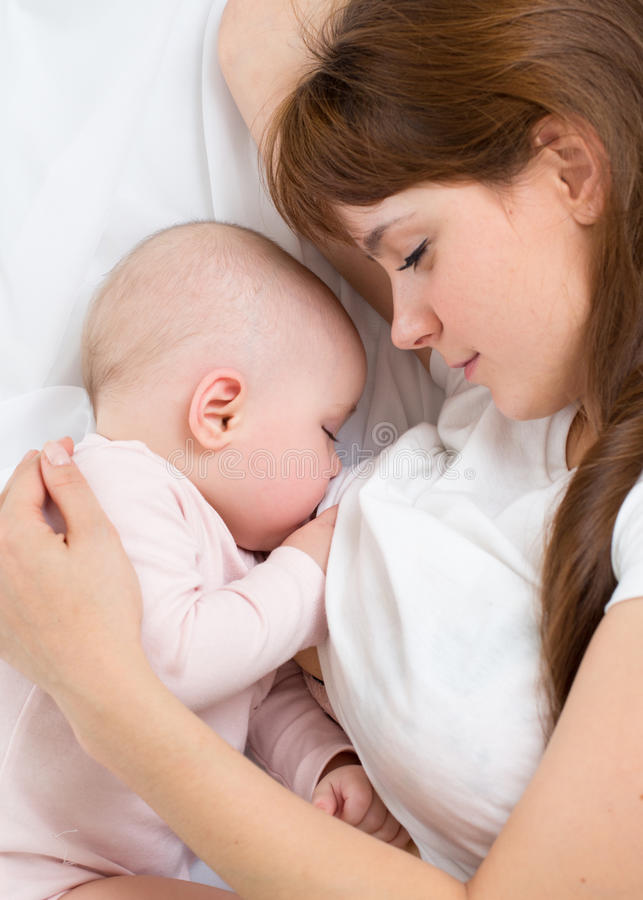 年轻母亲哺乳她的婴孩 哺乳 免版税库存图片