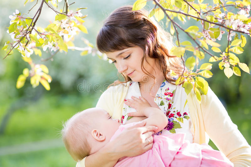 年轻母亲哺乳的女婴晴天 免版税库存照片