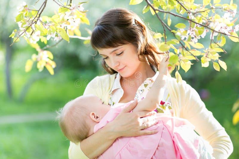 年轻母亲哺乳的婴孩在庭院里 免版税库存图片
