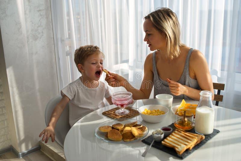 母亲哺养儿童早餐A明亮的晴朗的早晨 图库摄影