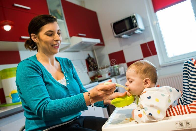 母亲哺养的婴孩第一坚实食物 食物多样化 图库摄影