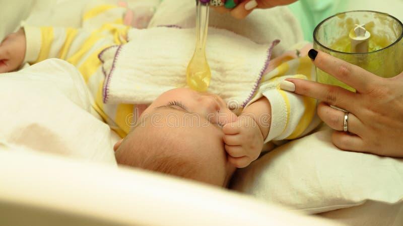 母亲哺养她的与匙子的小孩婴孩纯汁浓汤 库存照片