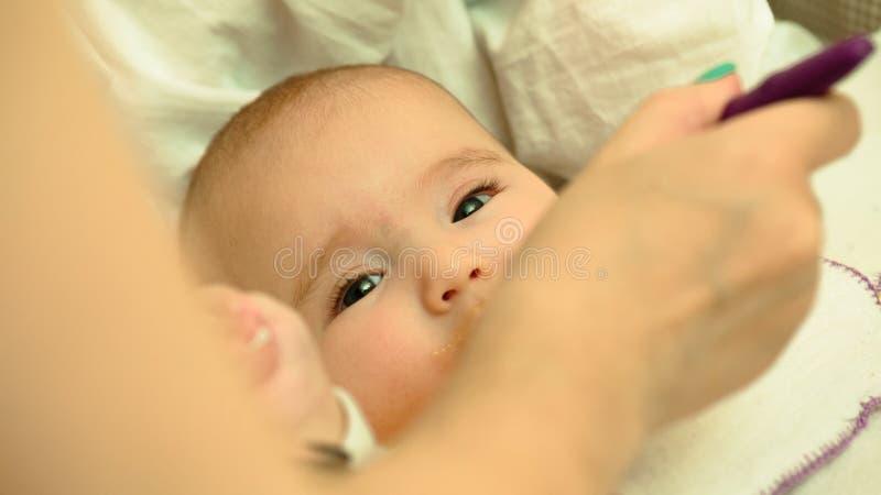 母亲哺养她的与匙子的小孩婴孩纯汁浓汤 免版税库存图片