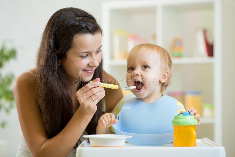 母亲喂养从匙子的婴孩 库存图片