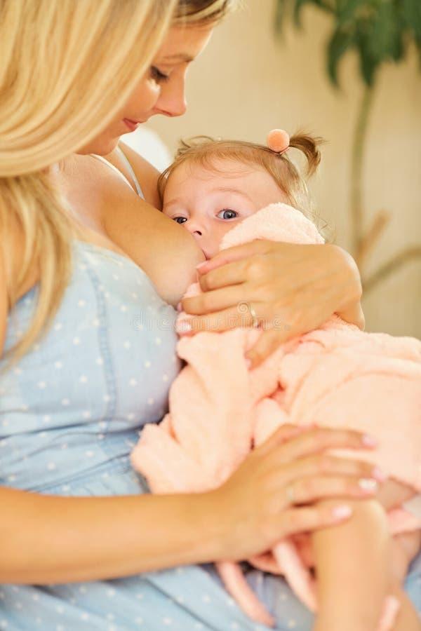 母亲喂养她的婴孩用乳奶 免版税库存图片