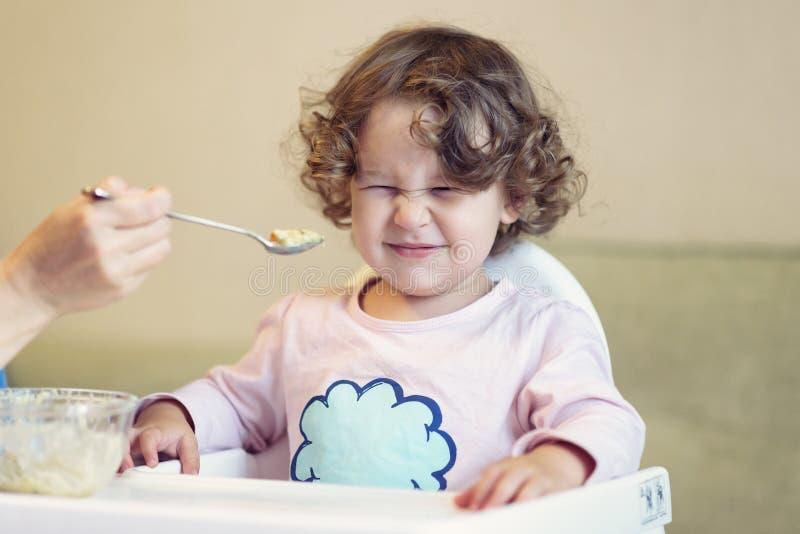 母亲喂养有匙子的婴孩 图库摄影