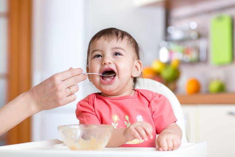 母亲喂养从匙子的滑稽的婴孩 免版税库存照片
