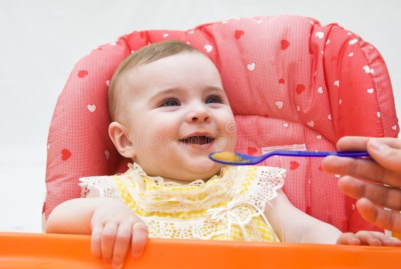母亲喂养从匙子的滑稽的婴孩 免版税库存图片