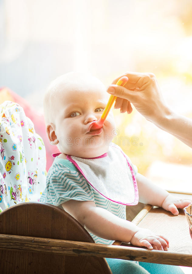 母亲喂养从匙子的滑稽的婴孩 库存照片