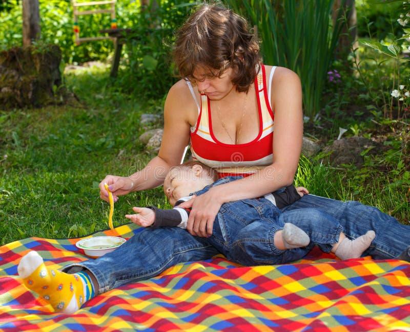 母亲喂养明亮的格子花呢披肩的孩子户外 库存图片