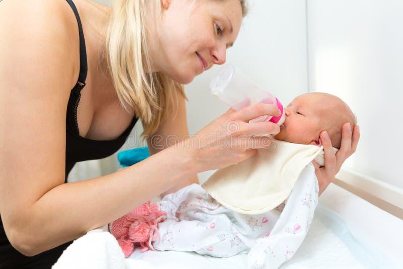 母亲喂养他们的有瓶的婴儿婴孩 免版税库存图片