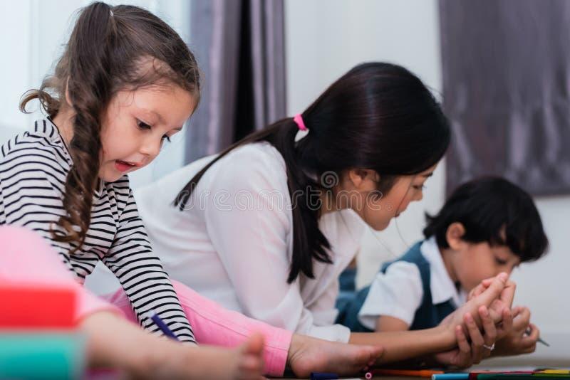 母亲图画班的教学孩子 与五颜六色的蜡笔颜色的女儿和儿子绘画在家 师范训练学生 免版税库存照片
