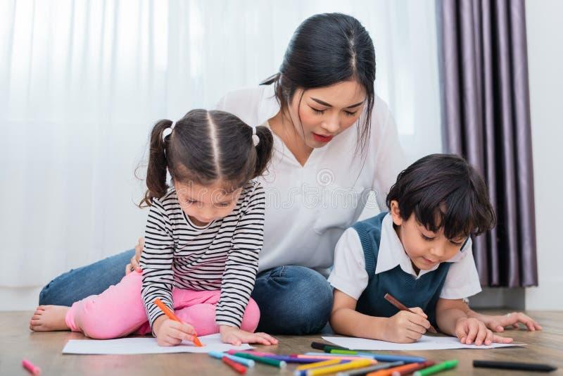 母亲图画班的教学孩子 与五颜六色的蜡笔颜色的女儿和儿子绘画在家 师范训练学生 图库摄影
