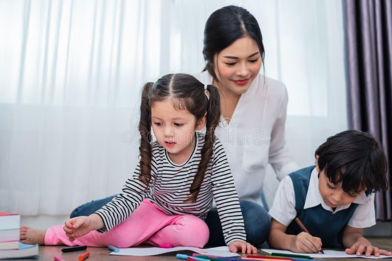 母亲图画班的教学孩子 与五颜六色的蜡笔颜色的女儿和儿子绘画在家 师范训练学生 库存图片