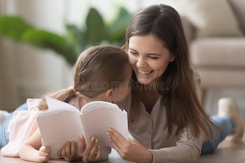 母亲在与女儿的温暖的木地板读了说谎的书 免版税库存图片