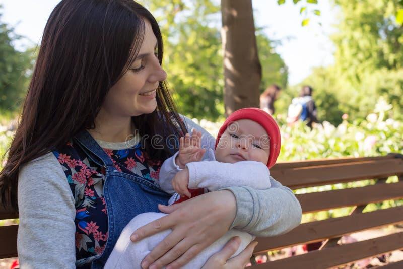 年轻母亲在公园抱着她的胳膊的一个新出生的婴孩步行的 免版税库存照片