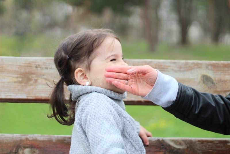 母亲在公园时握她的在她的女儿面颊的手,当坐一条长凳 库存图片