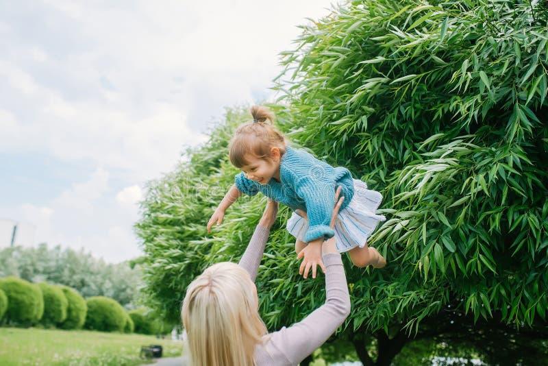 母亲在她的手上举行,投掷在她的手上的推力女儿在夏天在公园 妈妈和孩子本质上 免版税库存图片