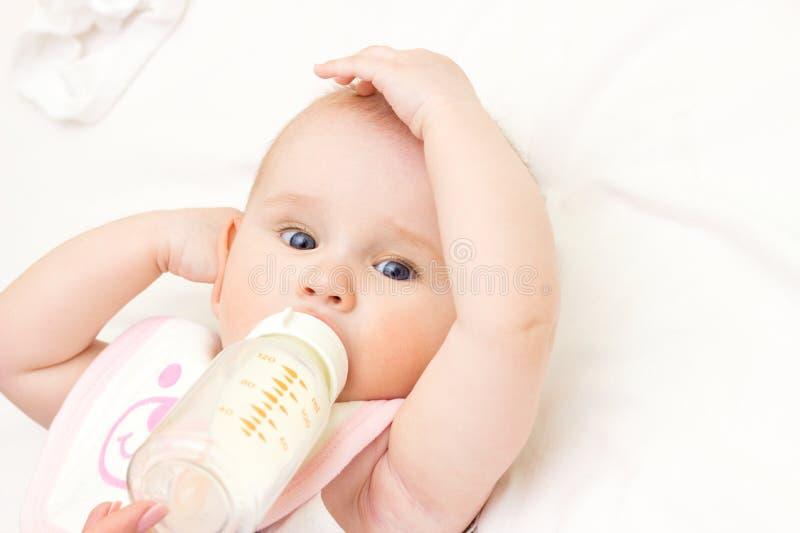 年轻母亲在室喂养她的婴孩 库存照片