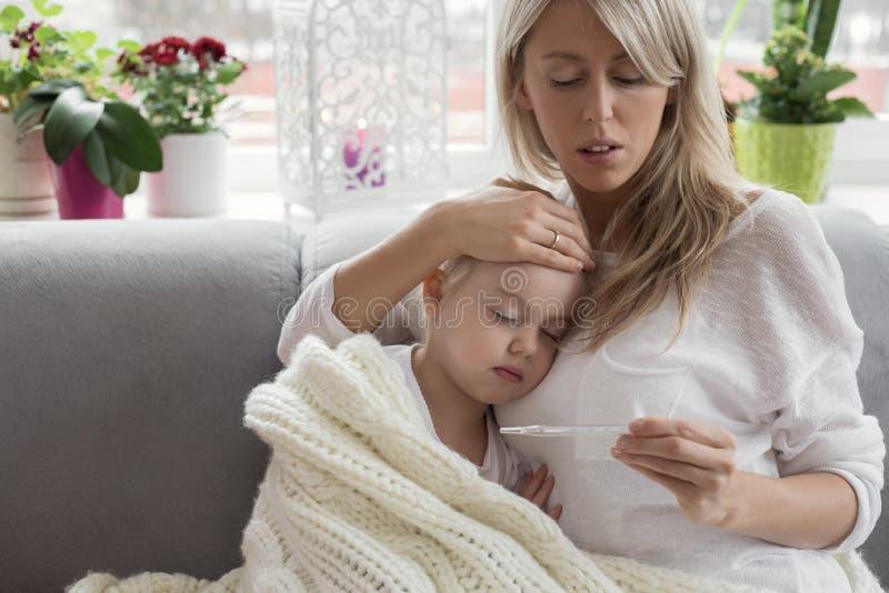 母亲在家和她病的孩子呆在一起 图库摄影