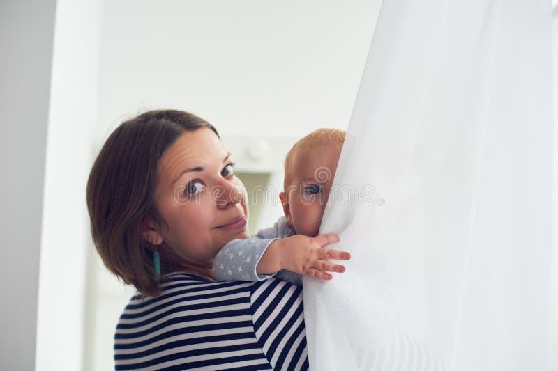 母亲在家继续肩膀笑的男婴 免版税图库摄影