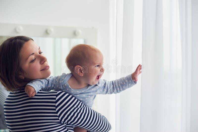 母亲在家继续肩膀笑的男婴 图库摄影