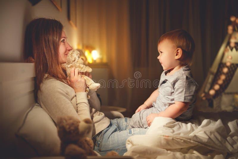 母亲在床上投入小儿子在晚上睡觉 库存图片