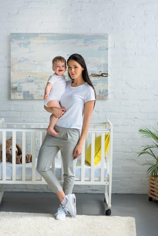 母亲在手上的抱着逗人喜爱的微笑的婴孩,当站立在婴孩小儿床时 免版税库存照片