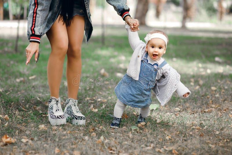 母亲在新鲜空气的一个春日握她的女儿的手,家庭在公园走并且开心 库存照片