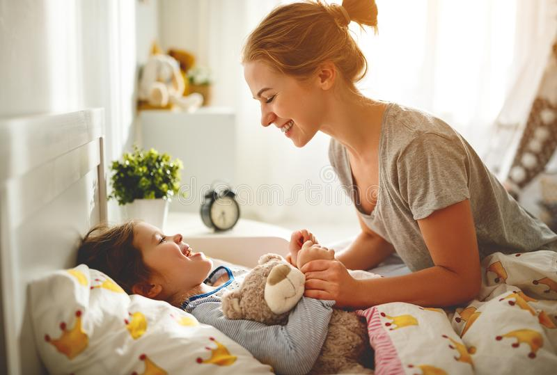 母亲在早晨在床上醒来她的女儿 库存照片