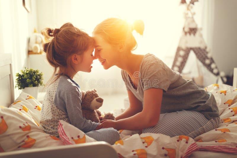 母亲在早晨在床上醒来她的女儿 免版税图库摄影