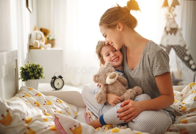 母亲在早晨在床上醒来她的女儿 免版税库存图片