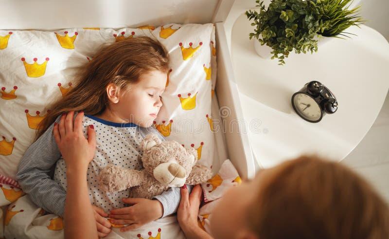 母亲在早晨在床上醒来她的女儿 库存图片